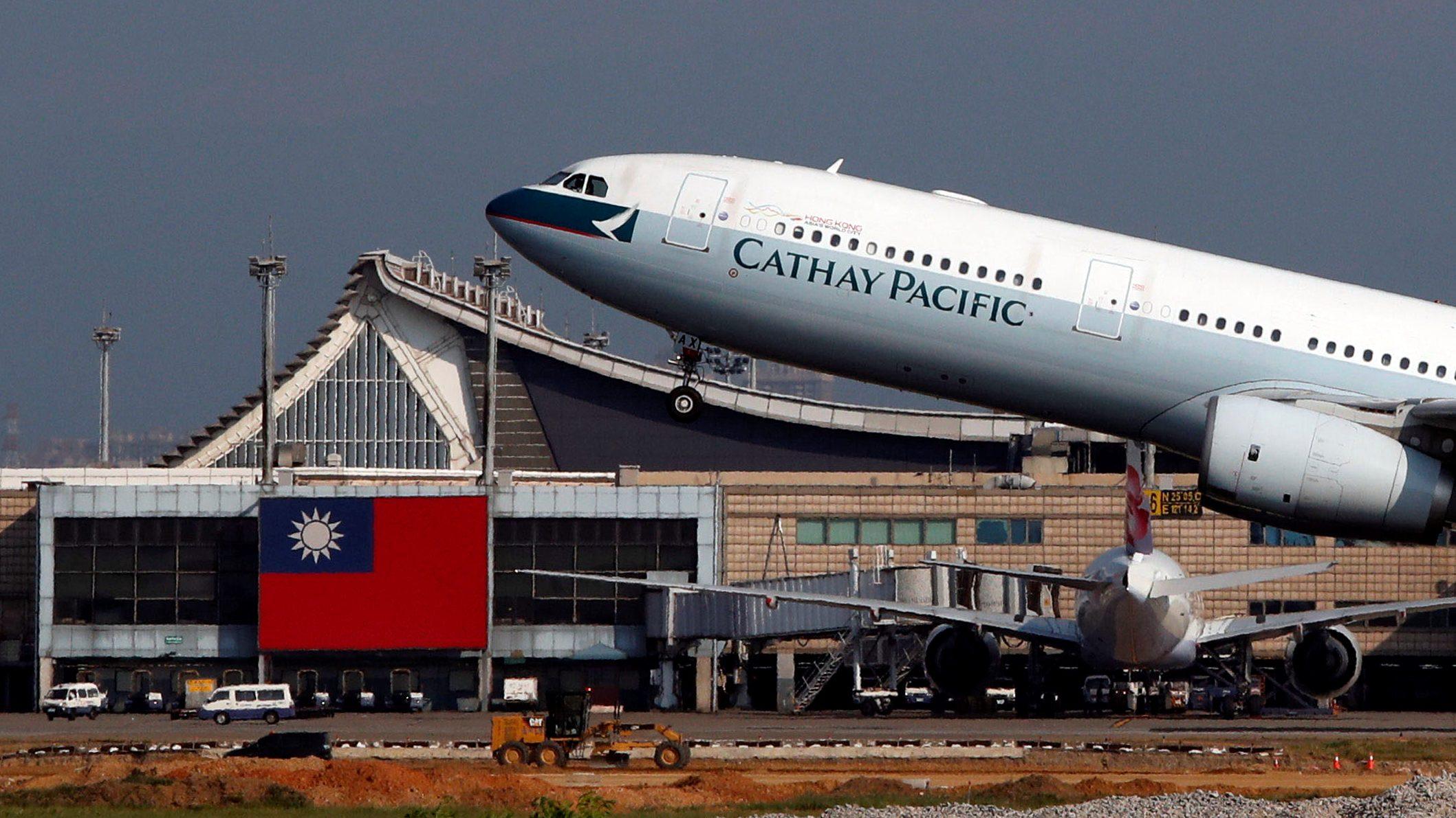 Hong Kong's Cathay Pacific Airways Airbus A330 passenger plane takes off near a Taiwanese national flag at Taoyuan International Airport