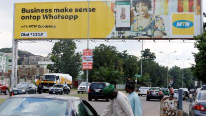 People stand near an advertising billboard for MTN telecommunication company along a street in Abuja