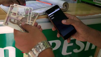 A customer conducts a mobile money transfer, known as M-Pesa, at a Safaricom agent stall, as he holds Kenyan shillings (KSh) in Nairobi, Kenya October 16, 2018.
