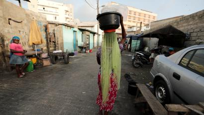 A street vendor carries a basin filled with water sachets in Dakar.