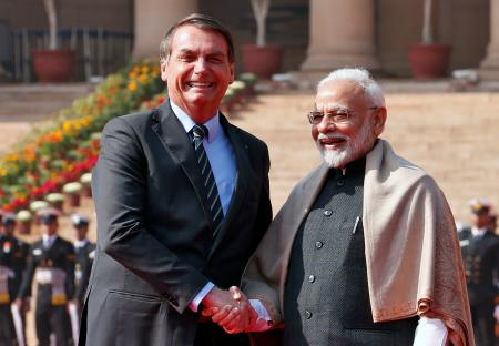 Brazil's President Bolsonaro shakes hands with India's Prime Minister Modi during his ceremonial reception at the forecourt of India's Rashtrapati Bhavan Presidential Palace in New Delhi