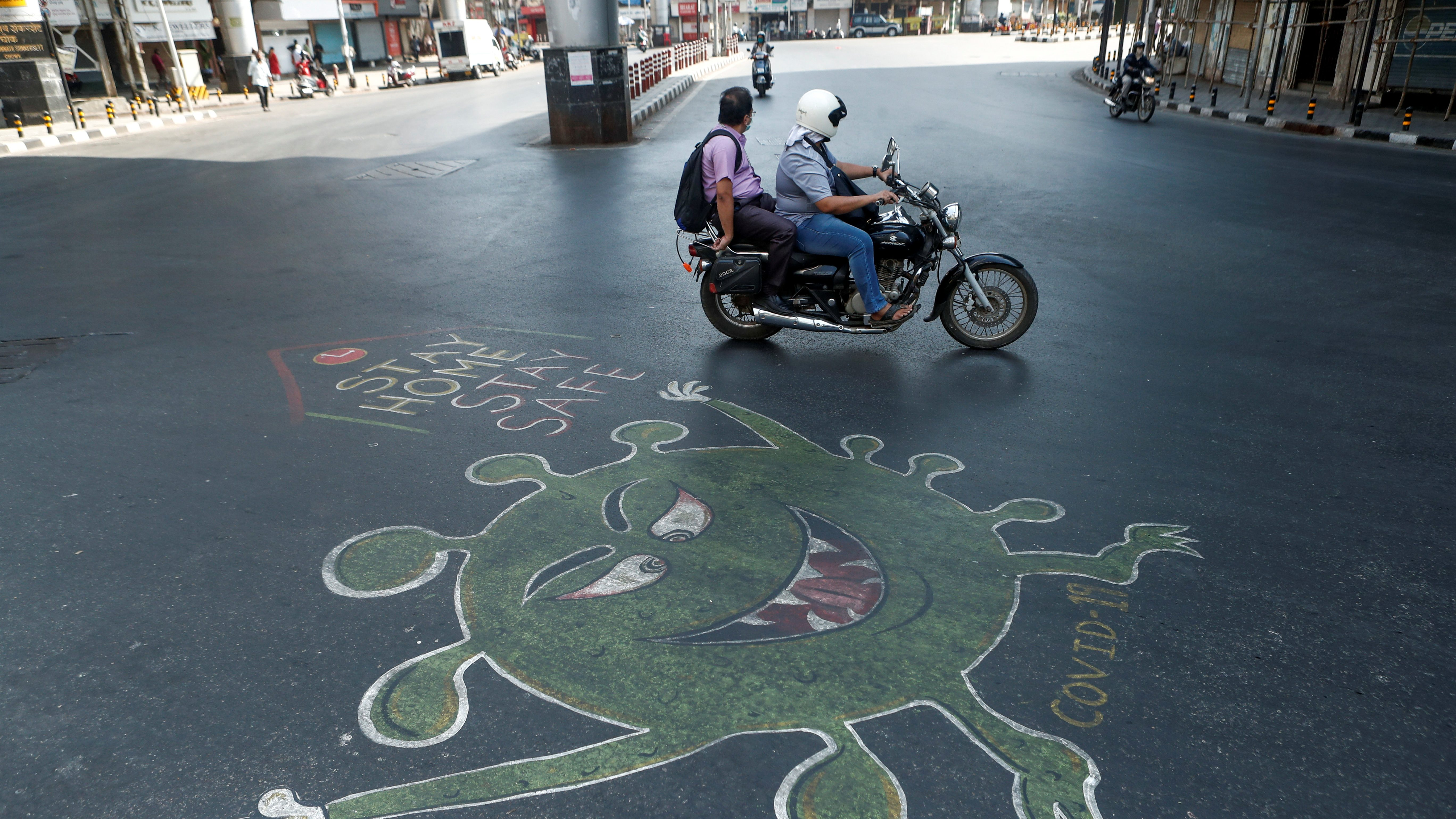 People ride past a graffiti on a road depicting the coronavirus, as an attempt to raise awareness about the importance of staying at home during a nationwide lockdown to slow the spreading of the coronavirus disease (COVID-19), in Mumbai