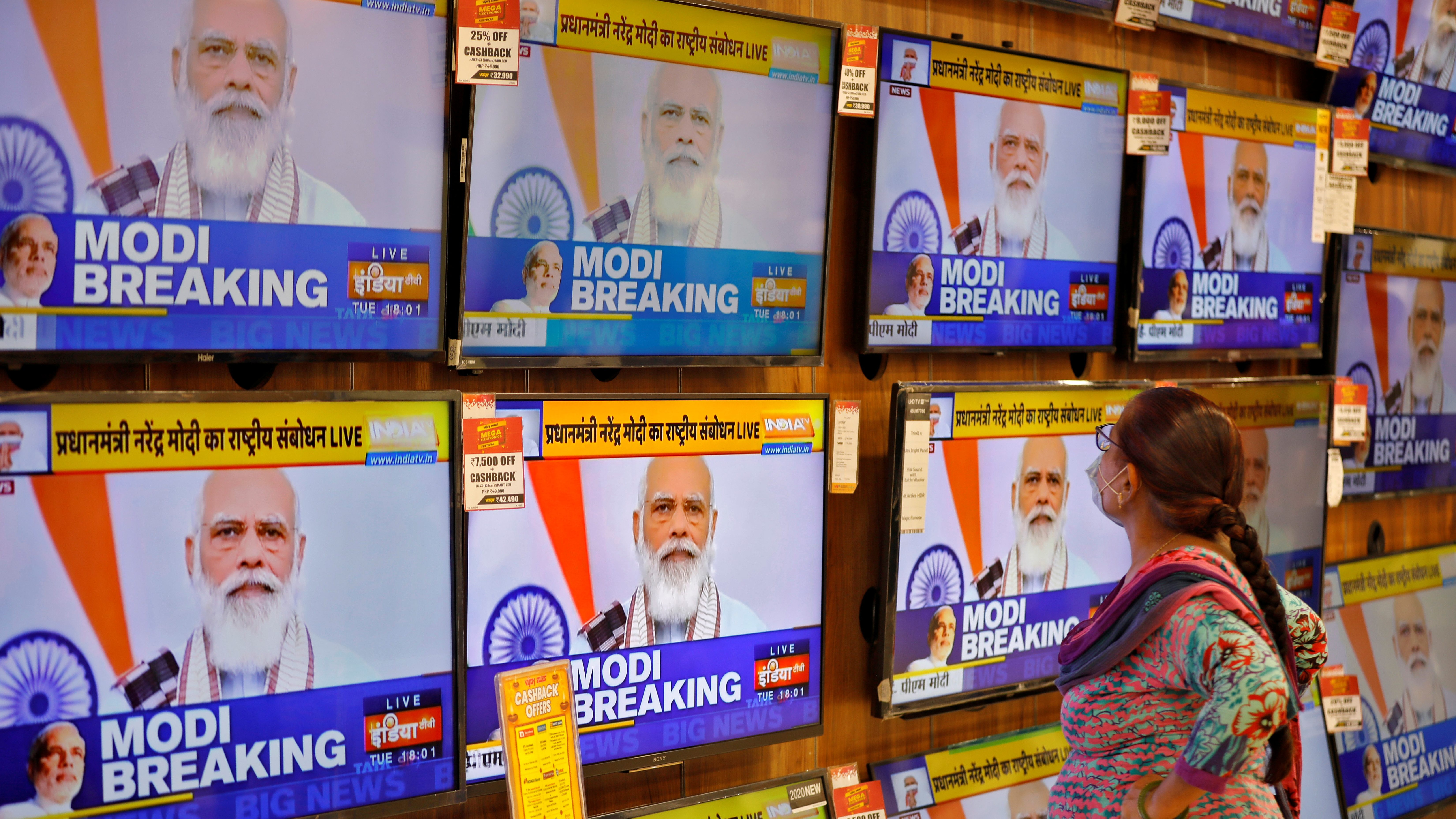 A woman wearing a protective mask watches Indian PM Modi on TV screens inside a showroom in Ahmedabad