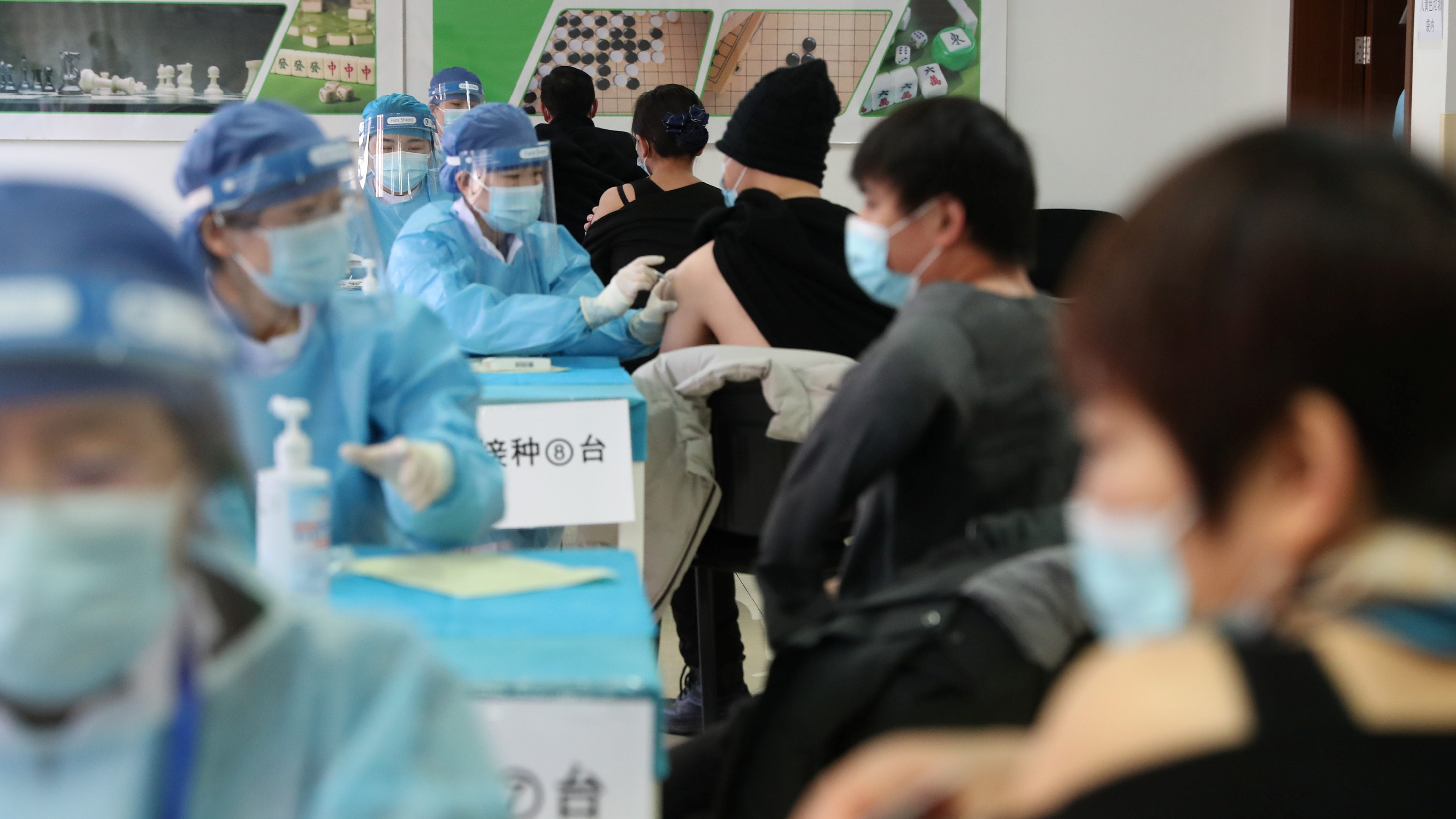 Medical workers administer COVID-19 vaccine at a makeshift vaccination site in Beijing