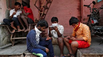 A group of boys in Mumbai look at their smartphones.