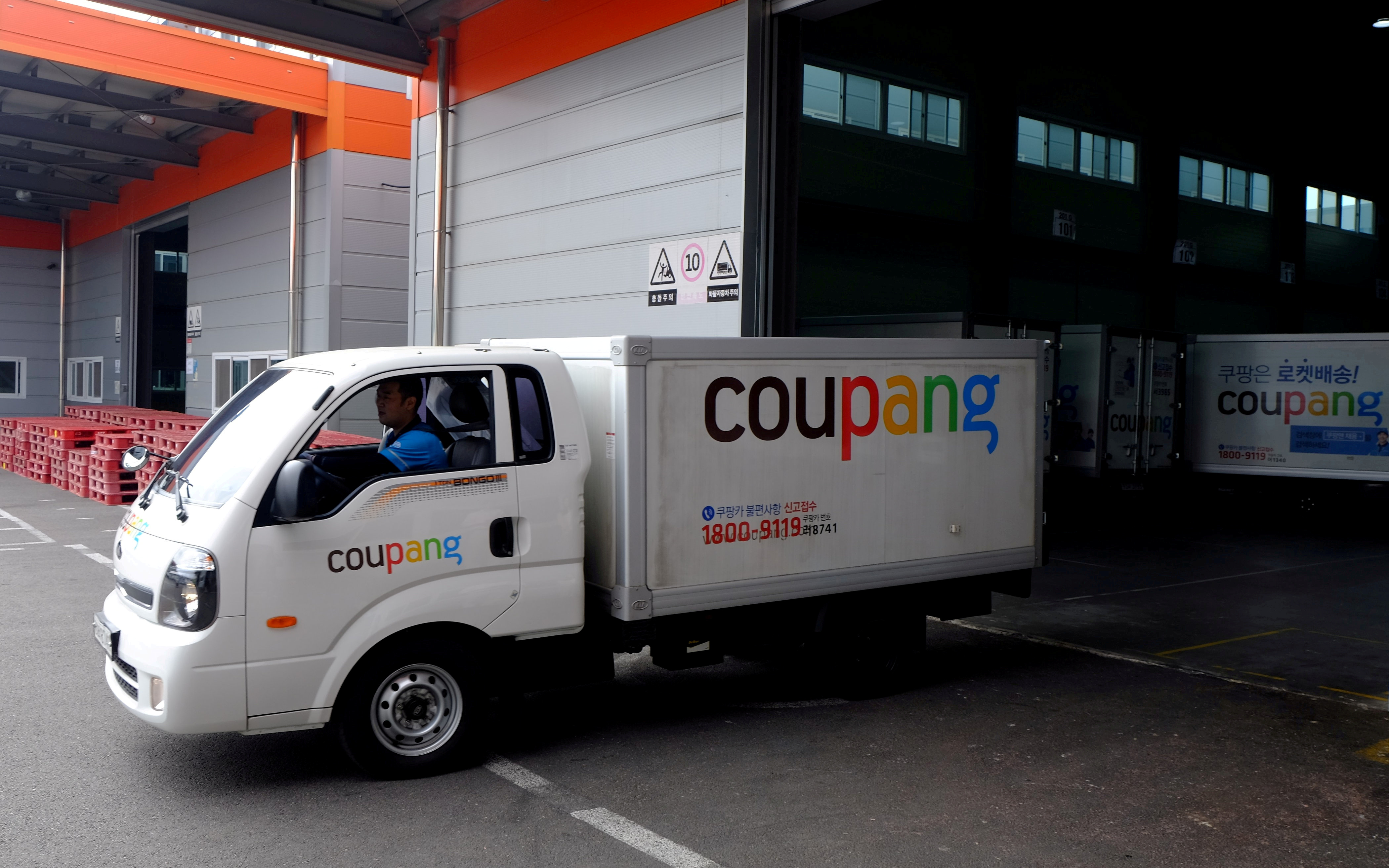 A Coupang delivery truck sets out for its destination.