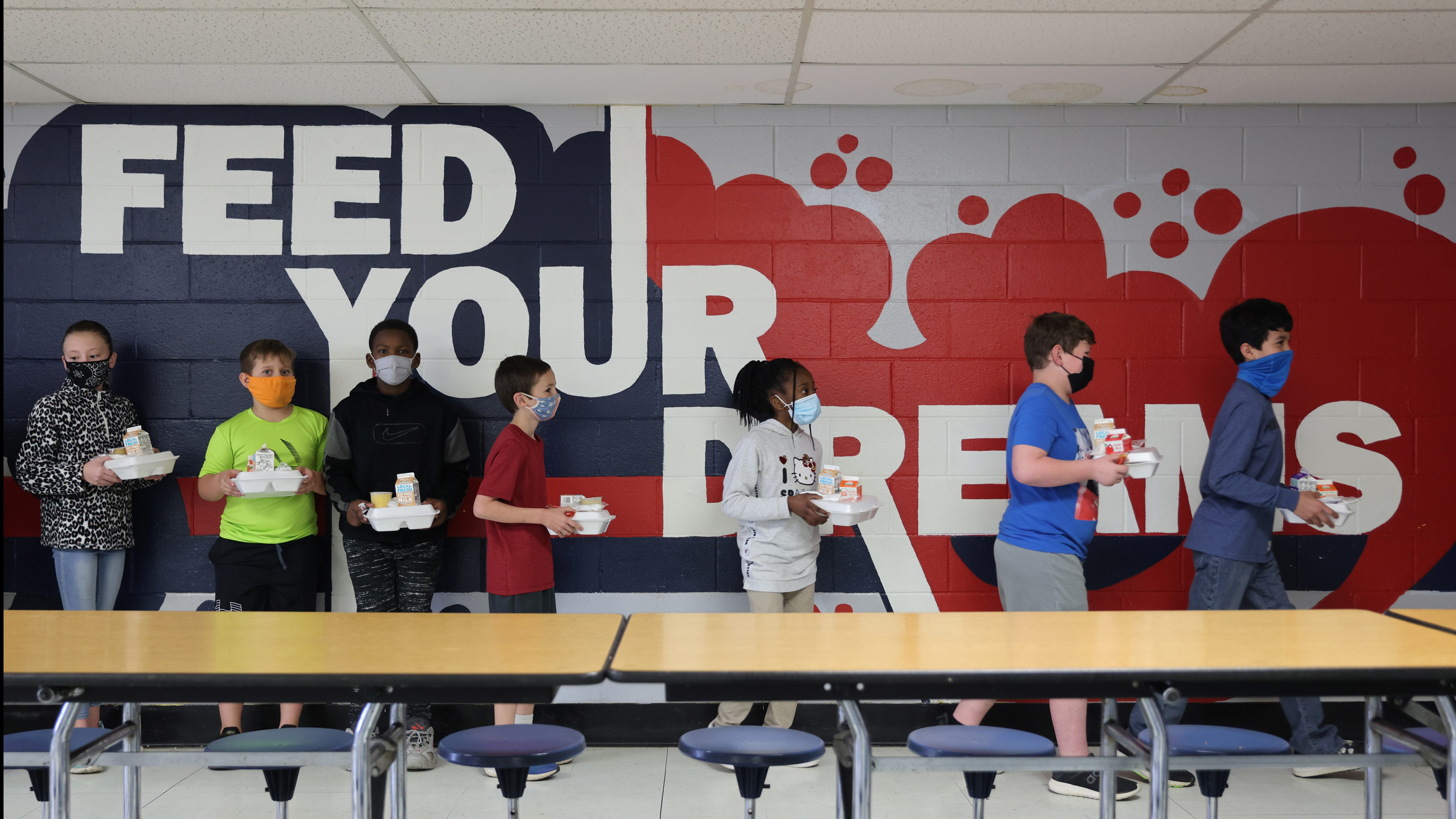 Older students carry their lunches to their classrooms to eat, leaving the lunchroom free for younger students to keep a social distance during in-person learning at Ackerman Elementary school in the small town of Ackerman, Mississippi, U.S.