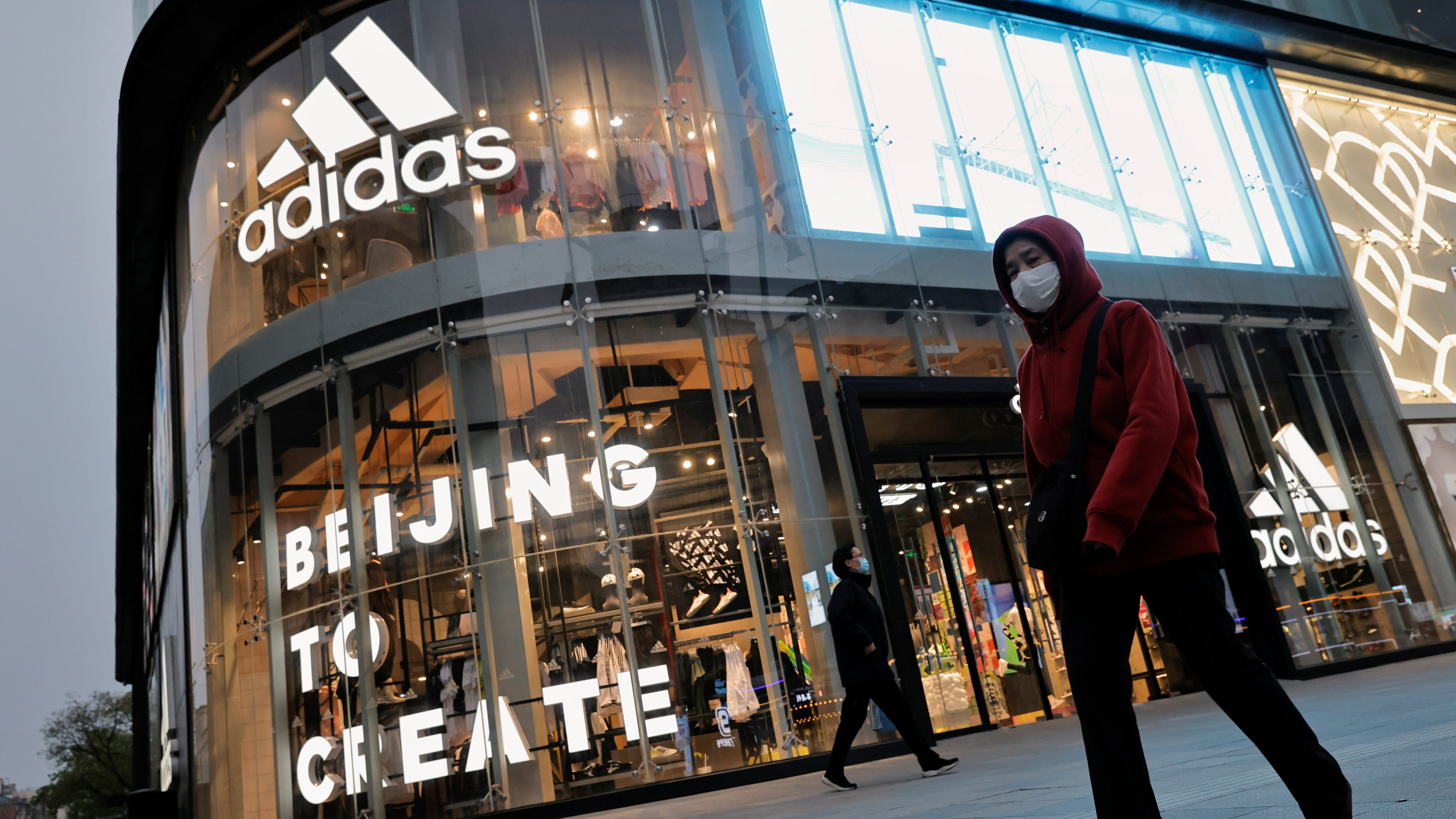 People walk past an Adidas store in a shopping district in Beijing