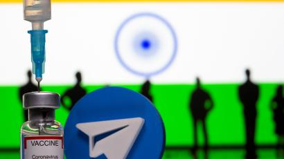 """A 3D-printed Telegram app logo, small toy figurines, a syringe and vial labelled """"coronavirus disease (COVID-19) vaccine"""" are seen in front of India flag in this illustration"""