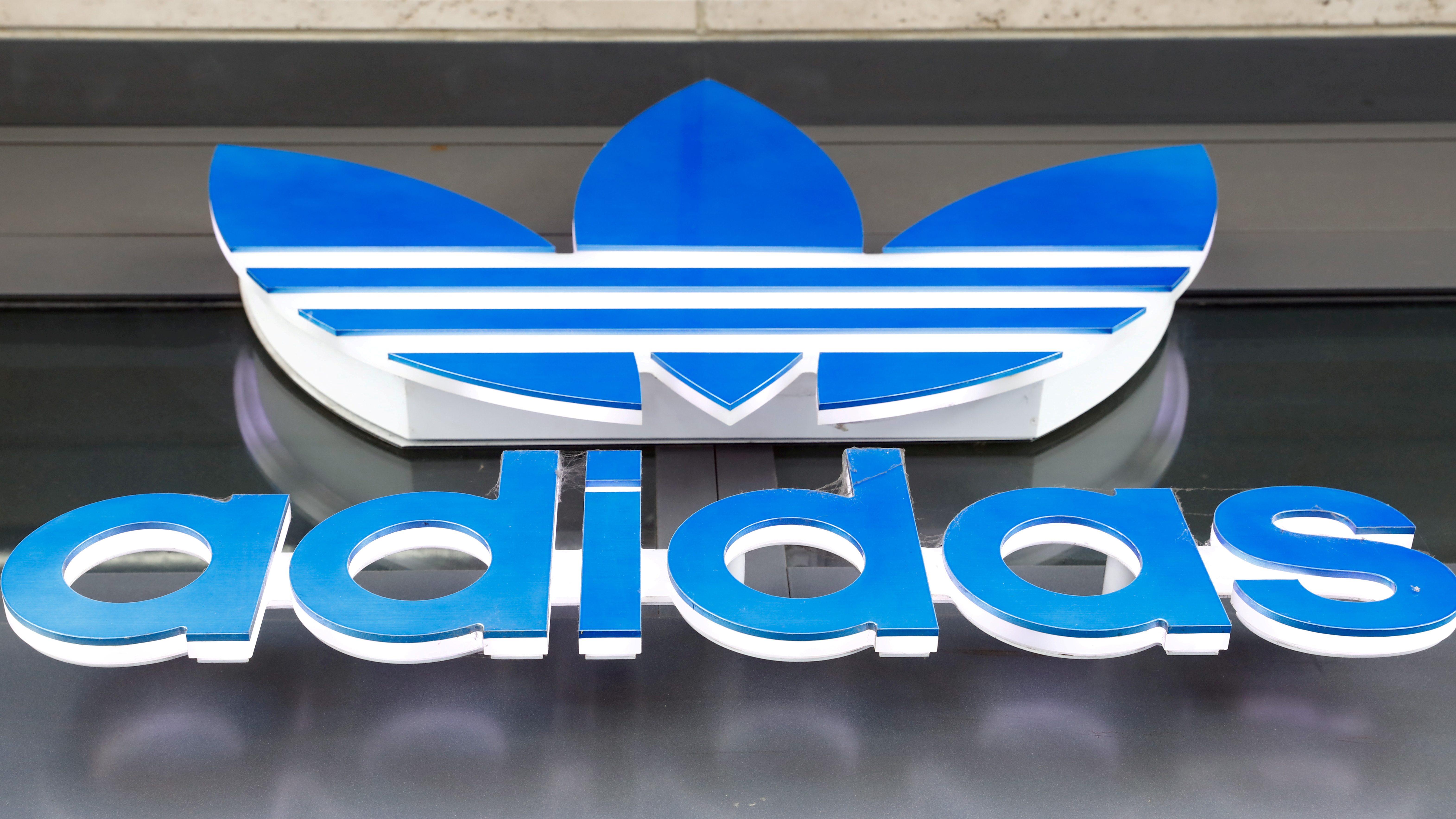 A photograph of an adidas store sign logo