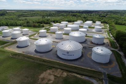 An aerial view of several large, cylindrical fuel holding tanks set against a backdrop of fields and trees.