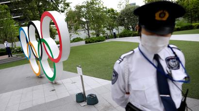Security personnel stand guard near the Olympic rings monument during a rally by anti-Olympics protesters outside the Japanese Olympic Committee headquarters, amid the coronavirus disease (COVID-19) outbreak, in Tokyo, Japan May 18, 2021. REUTERS/Issei Kato