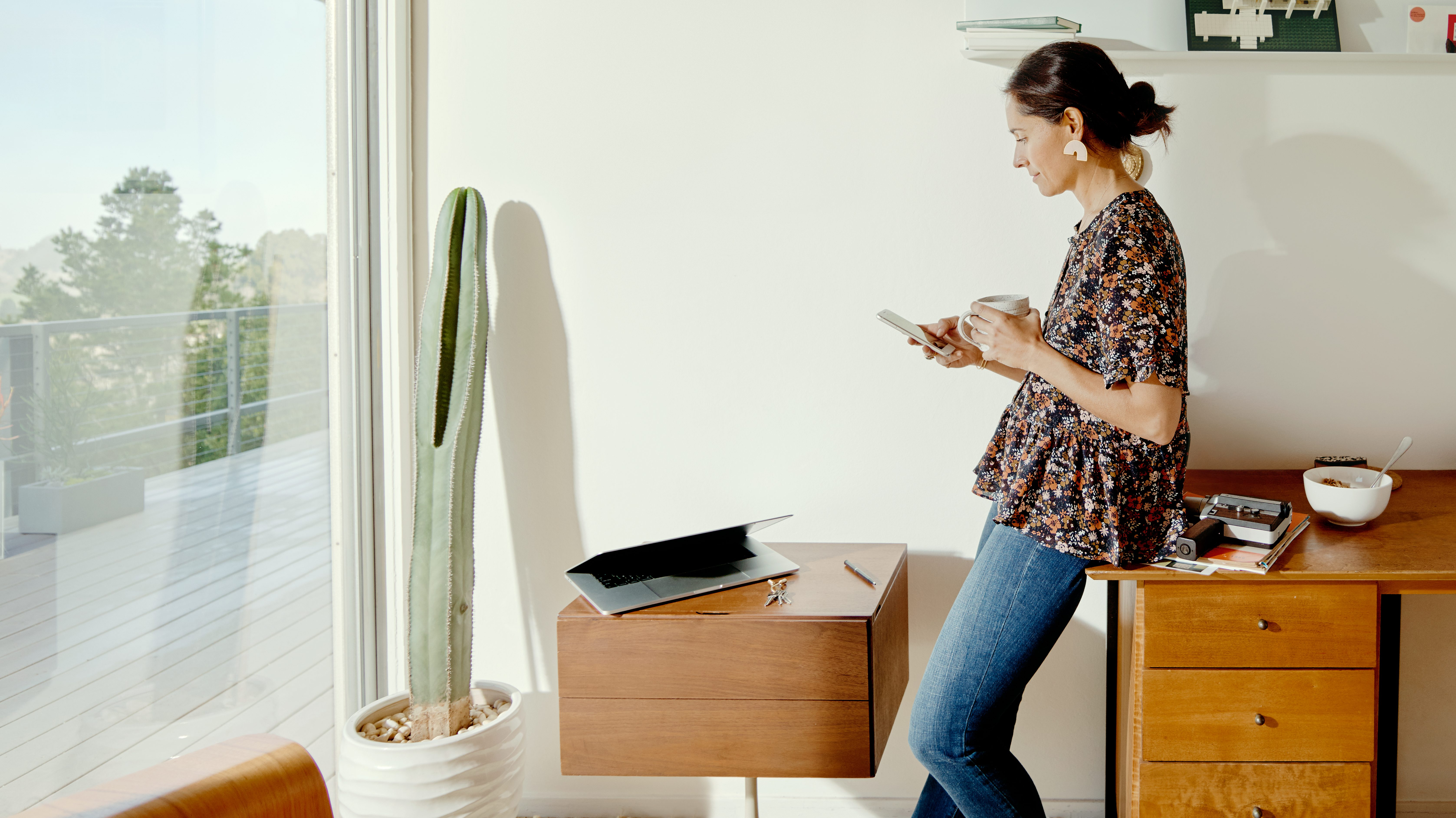 A woman uses her phone in a sunlit home with Southwest decor
