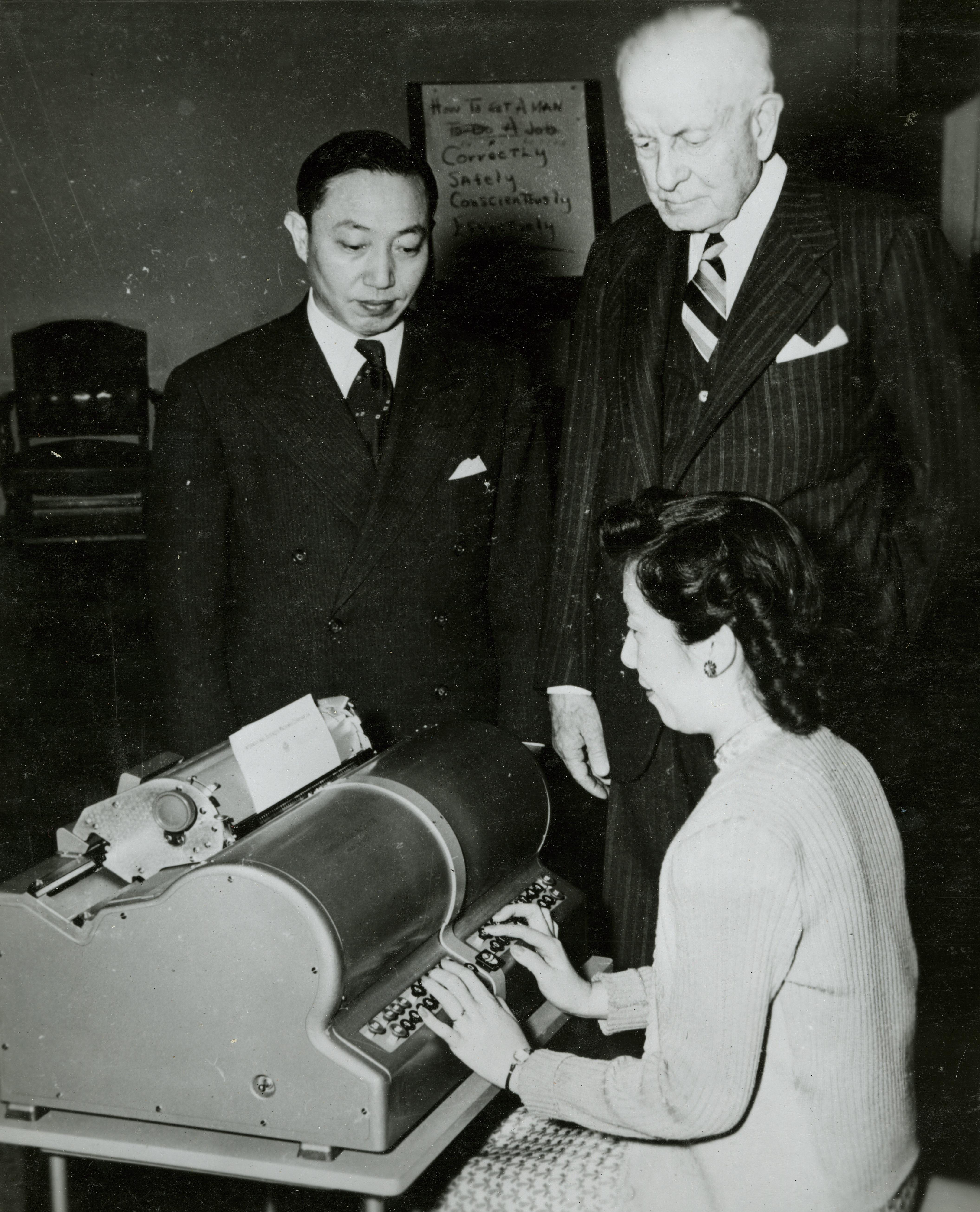 A woman types on Kao's Chinese electric typewriter, as IBM president Thomas J. Watson looks on.