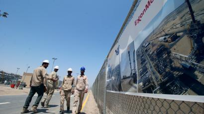 Iraqi staff from the West Qurna-1 oilfield, which is operated by ExxonMobil, walk during the opening ceremony near Basra in 2019