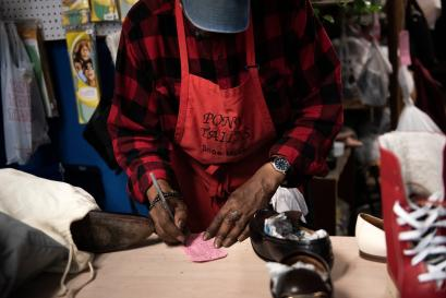 A Black shoemaker in Washington, DC writes on a piece of paper.