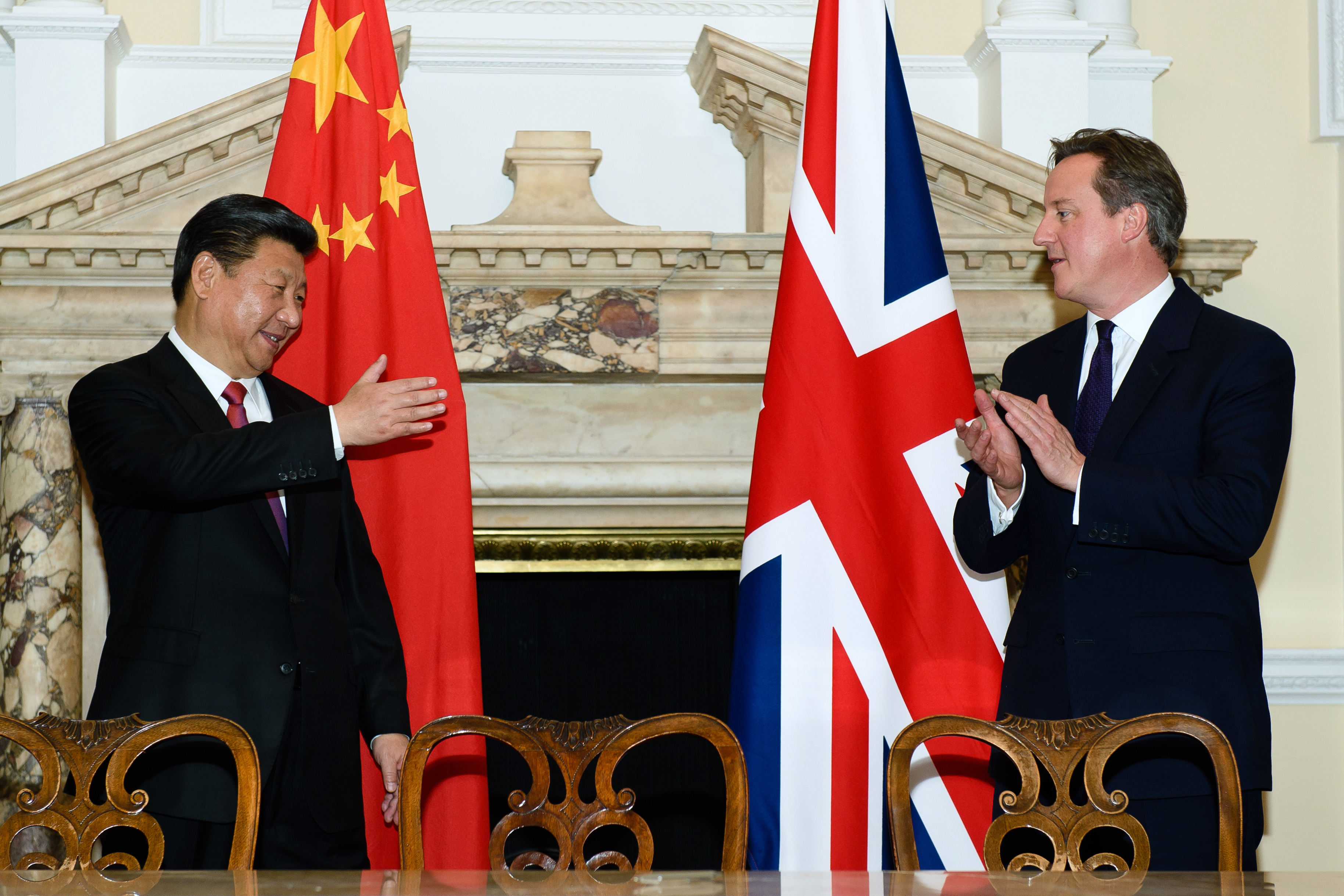 David Cameron and Xi Jinping applaud in front of their countries' flags during a commercial contract exchange in 2015.