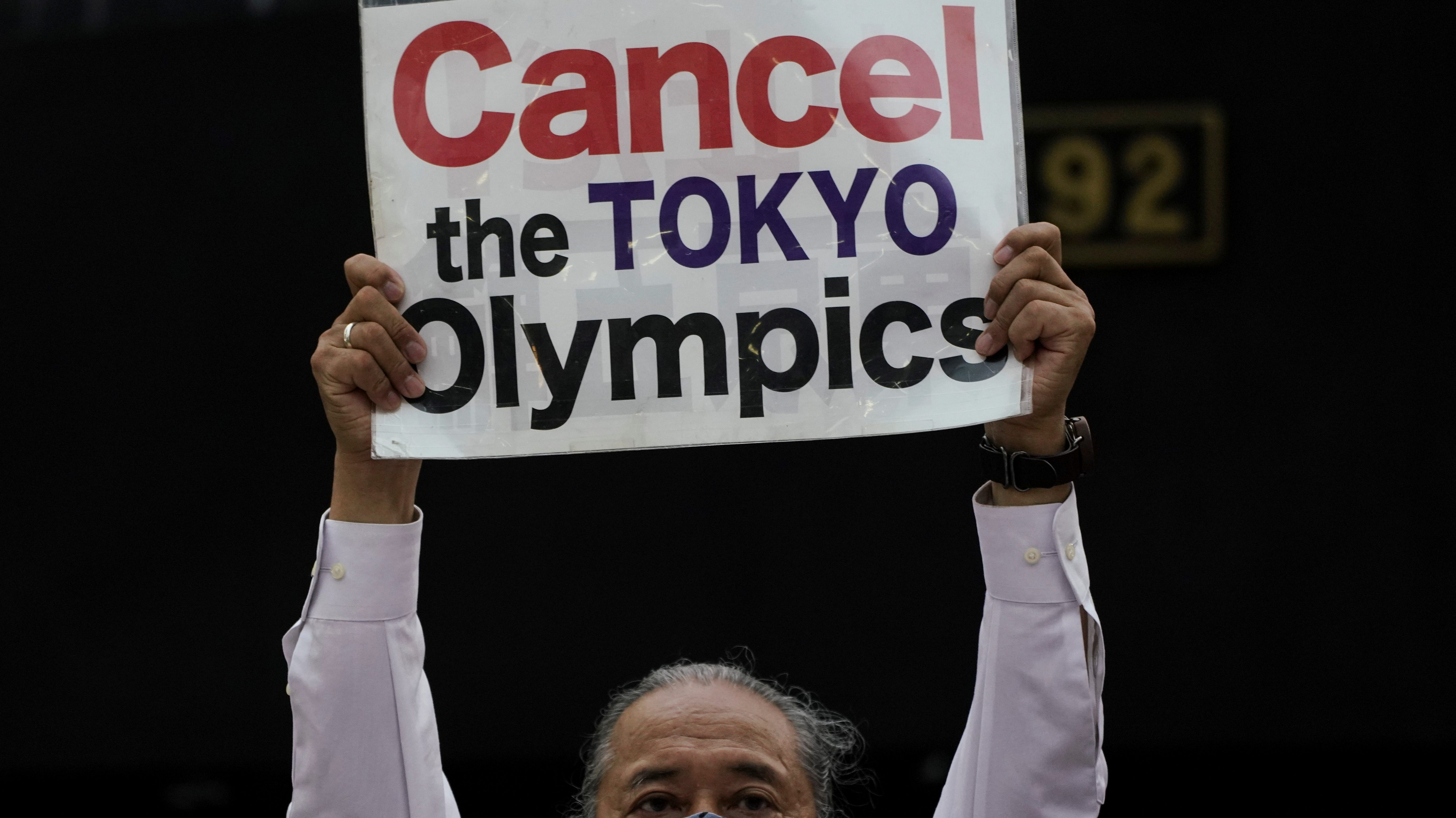 A protester holds up a banner calling for the Olympic Games to be canceled