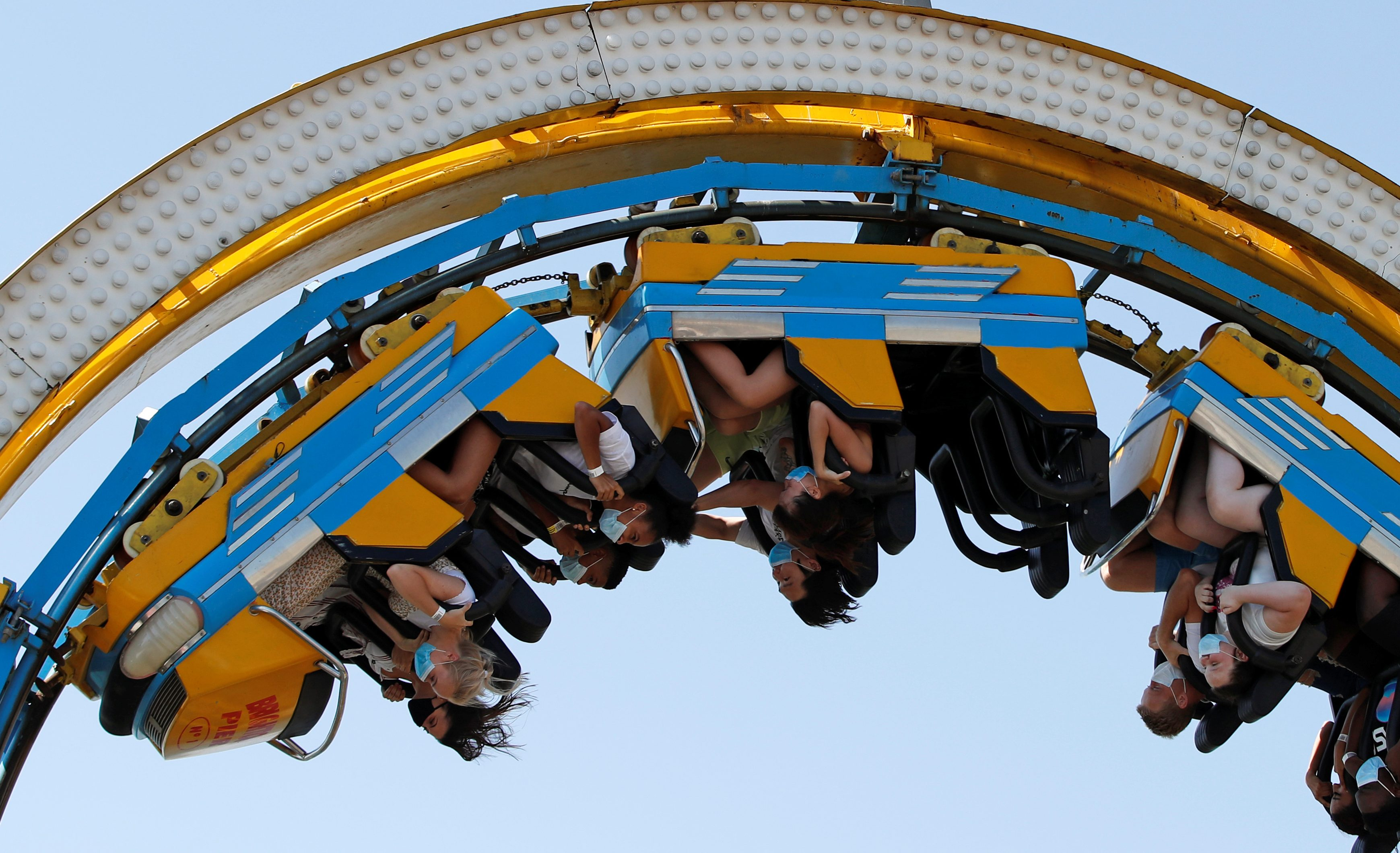 People wearing protective face masks ride a roller coaster as they enjoy the sunny weather at the Brighton Palace Pier