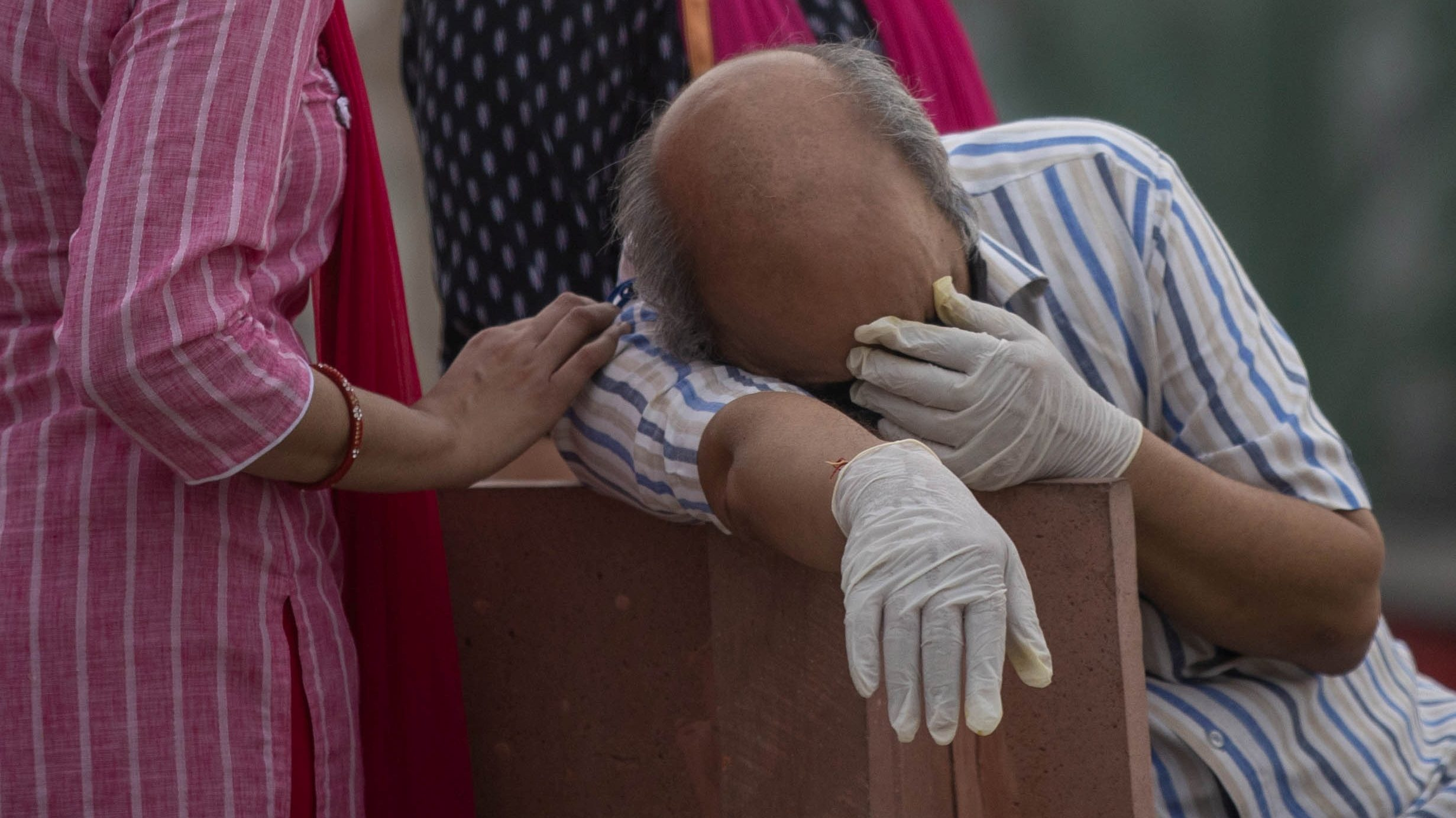A man reacts before the cremation of his relative, who died from the coronavirus disease (COVID-19), on the banks of the river Ganges at Garhmukteshwar