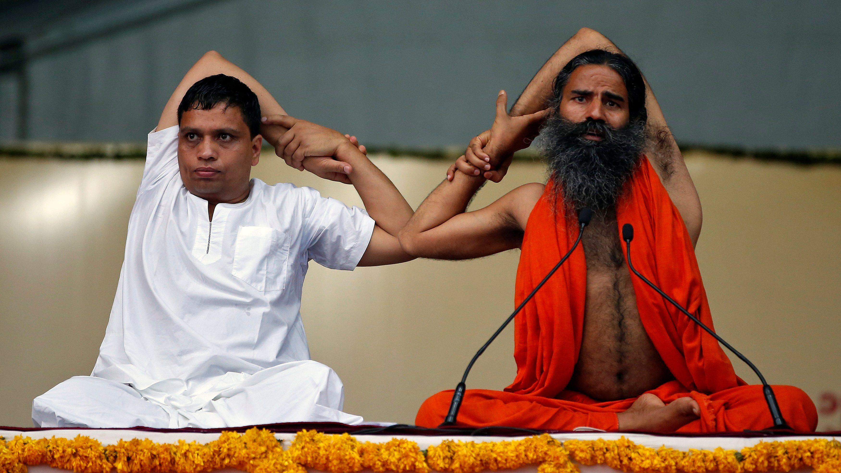 Yoga guru Baba Ramdev and Managing Director ofPatanjali Ayurved Acharya Balkrishna perform yoga during a four-day long camp ahead of International Yoga day, in Ahmedabad