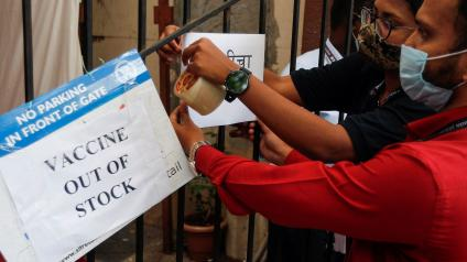 Health workers attach a notice on the shortage of COVID-19 vaccine supplies at a vaccination centre in Mumbai