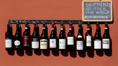 Wine bottles displayed hanging from a rack outside store