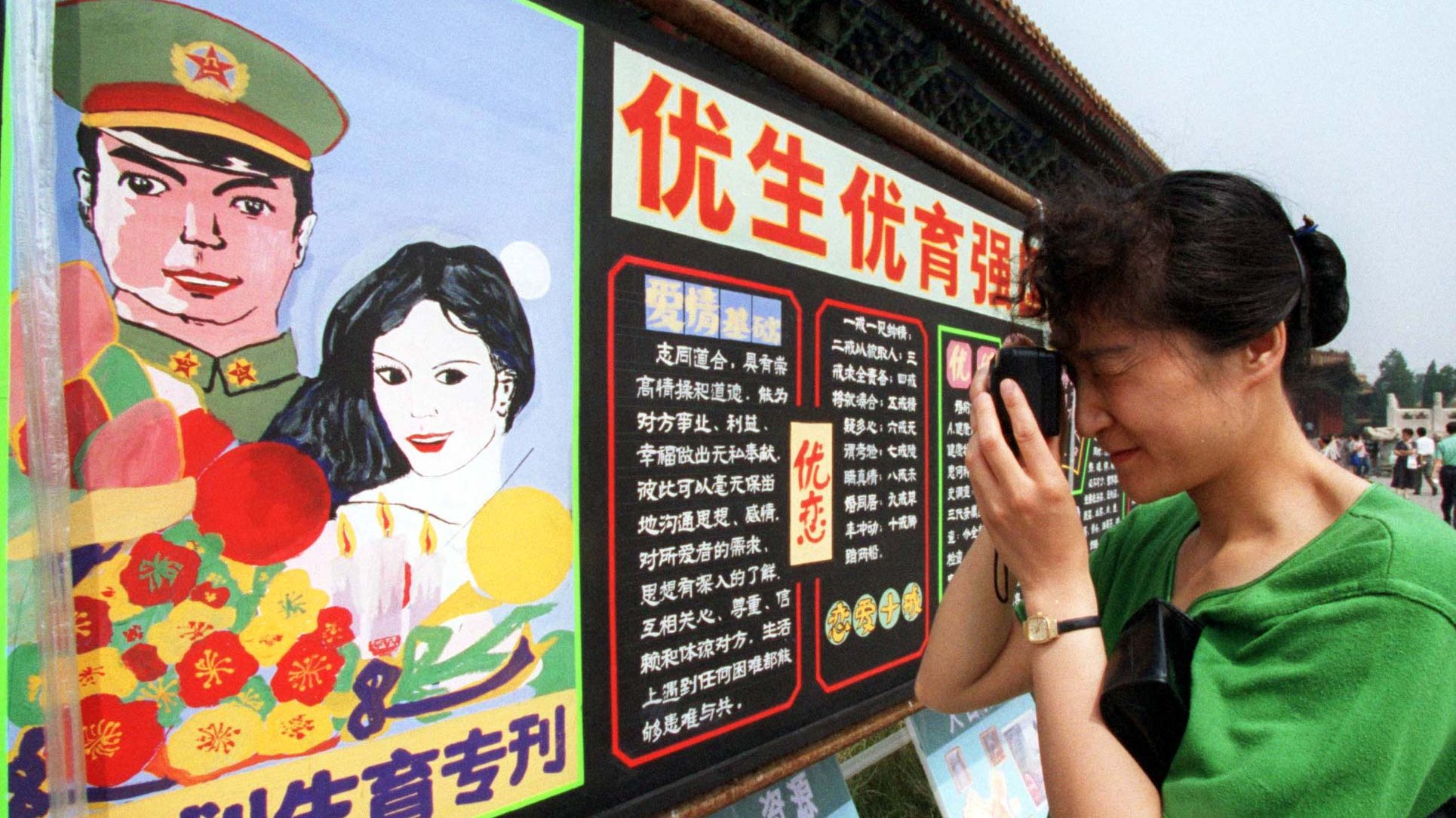 """A visitor to a World Population Day exhibition in Beijing takes a photo of a propaganda billboard encouraging people to follow China's family planning policies, July 10, 1998. One slogan says, """"One is too few, while two are just right."""""""