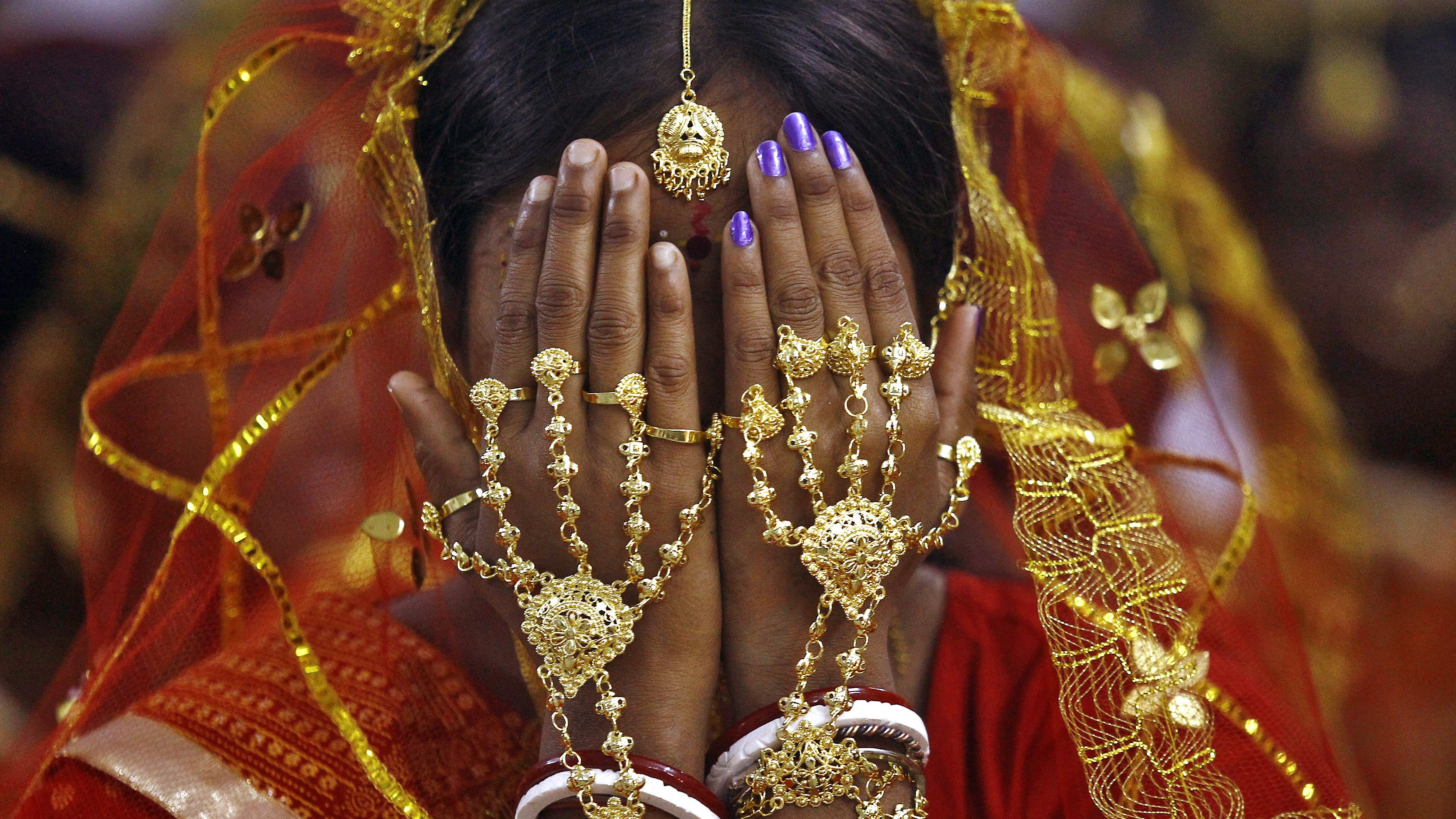 A bride covers her face as she waits to take her wedding vow at a mass marriage ceremony at Bahirkhand village, north of Kolkata