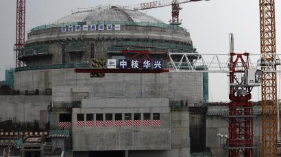 Workers (bottom) stand in front of a nuclear reactor as part of the Taishan Nuclear Power Plant seen under construction in Taishan, Guangdong province, October 17, 2013. As China signs global deals to export its nuclear power technology, it faces a huge obstacle: it still needs to show it can build and safely operate these reactors at home. Aided by foreign technology acquired during three decades of development, China has the highest number of reactors being built and ambitions to export its home-grown models to an overseas market worth hundreds of billions of dollars. Picture taken October 17, 2013. REUTERS/Bobby Yip (CHINA - Tags: ENERGY ENVIRONMENT SCIENCE TECHNOLOGY BUSINESS)