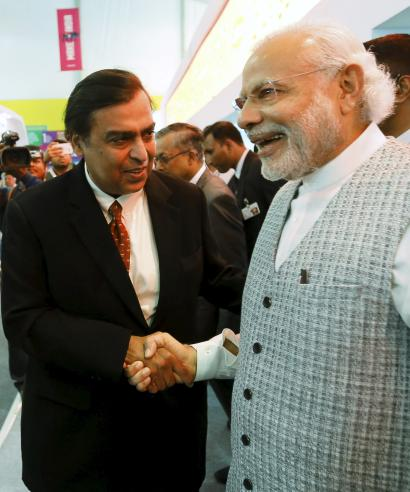 India's Prime Minister Narendra Modi shakes hand with Mukesh Ambani, chairman of Reliance Industries Limited during a visit to a pavilion at the exhibition centre of the 'Make In India' week in Mumbai