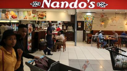 Shoppers walk past South African fast-food chain Nando's at a mall in Johannesburg, South Africa.