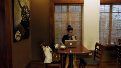 Woman drinks coffee while working on her laptop at Java Lounge coffee shop in Colombo