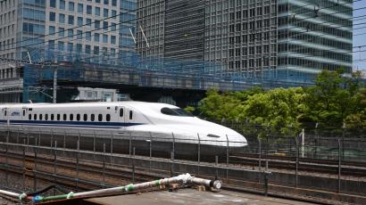 A high-speed train moves on tracks in front of office tower buildings