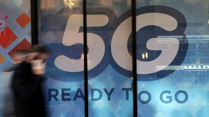 A man walks past a 5G sign in Monaco