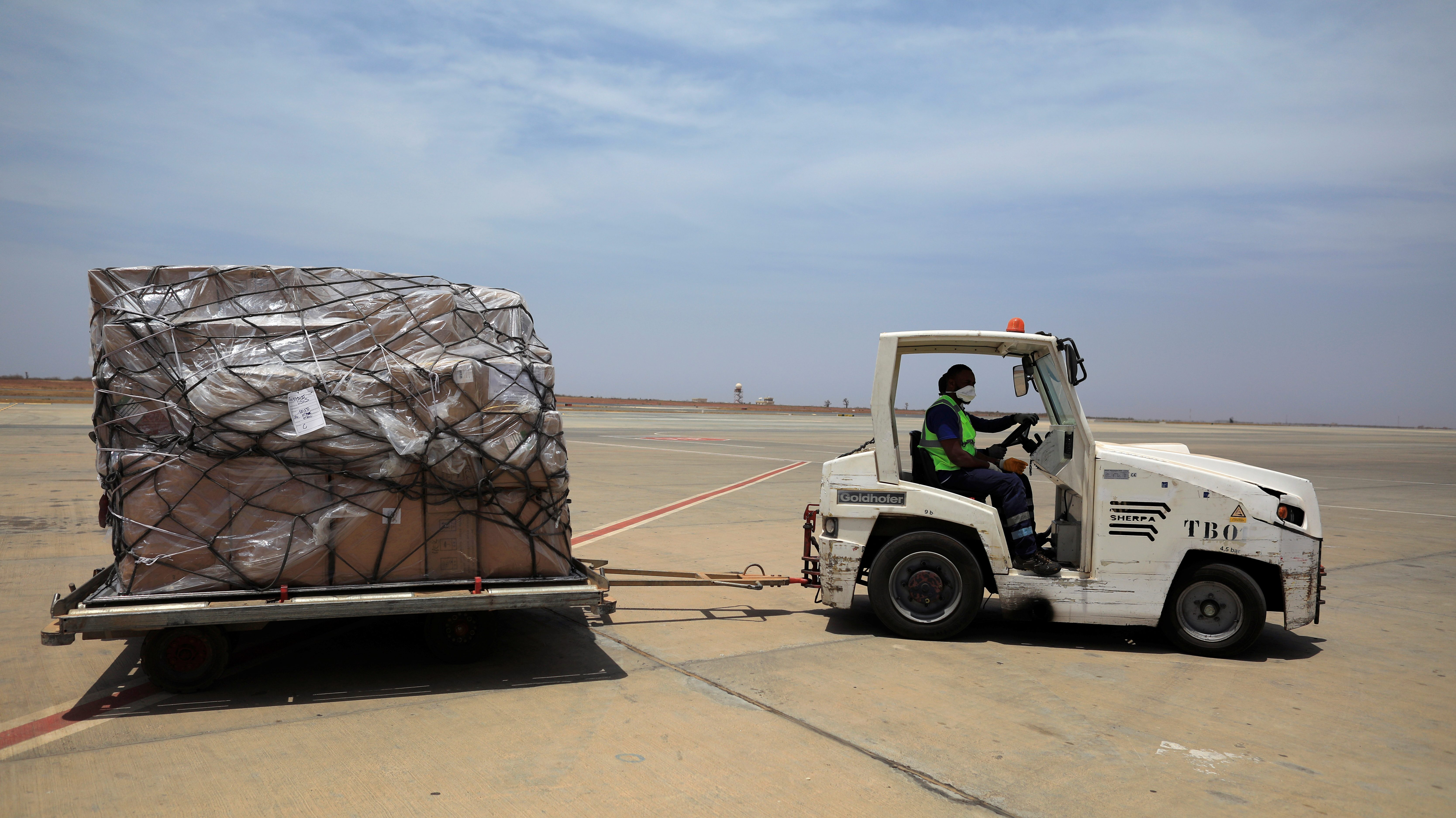 Airport workers drive a cart with shipment of medical supplies donated to help Africa for fight with the coronavirus disease (COVID-19) from Chinese billionaire Jack Ma and the Alibaba Foundation, after it arrived from Ethiopia at Blaise Diagne international airport in Thies, Senegal March 28, 2020.