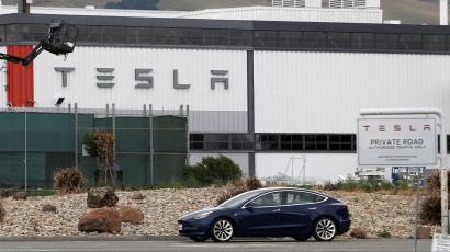 A Tesla vehicle drives past Tesla's primary vehicle factory in Fremont, California.