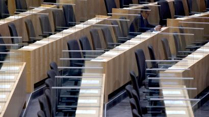A member of the parliament sits between plexiglass shields ahead of the budget speech at the parliament in Vienna