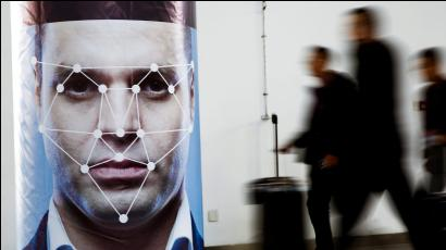 People walk past a poster simulating facial recognition software