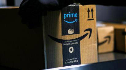 An Amazon worker delivers a package with Prime branding