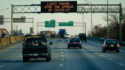 FILE PHOTO: A highway sign on Interstate 75 advises travelers to limit travel in order to slow the spread of the novel coronavirus (COVID-19), taken through a vehicle window, in Cincinnati