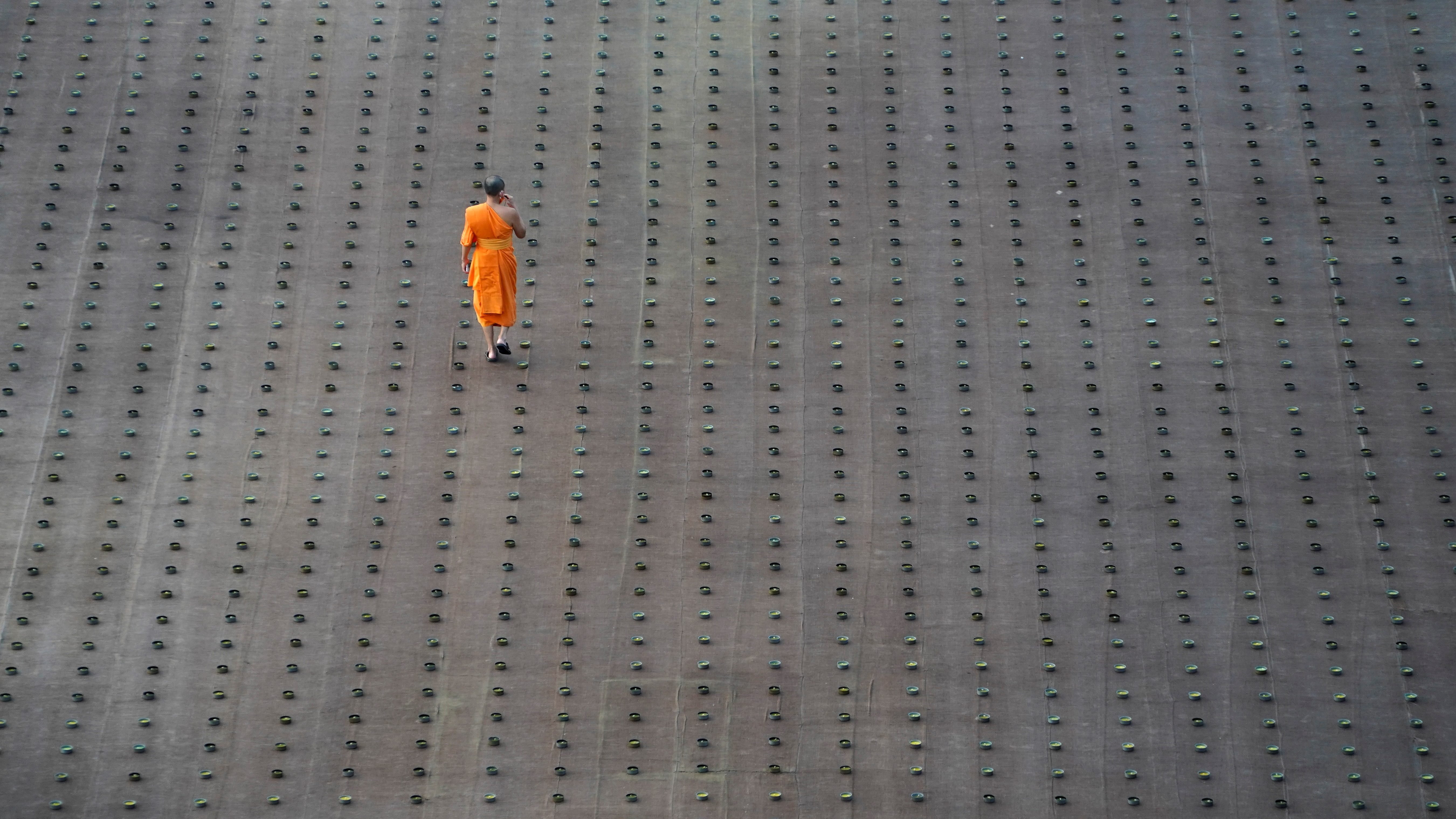 A Buddhist monk walks among candles prepared to be lit as 330,000 of them are arranged in the shape of the earth to set a Guinness World Record during Earth Day, at the Dhammakaya temple in Pathum Thani provine