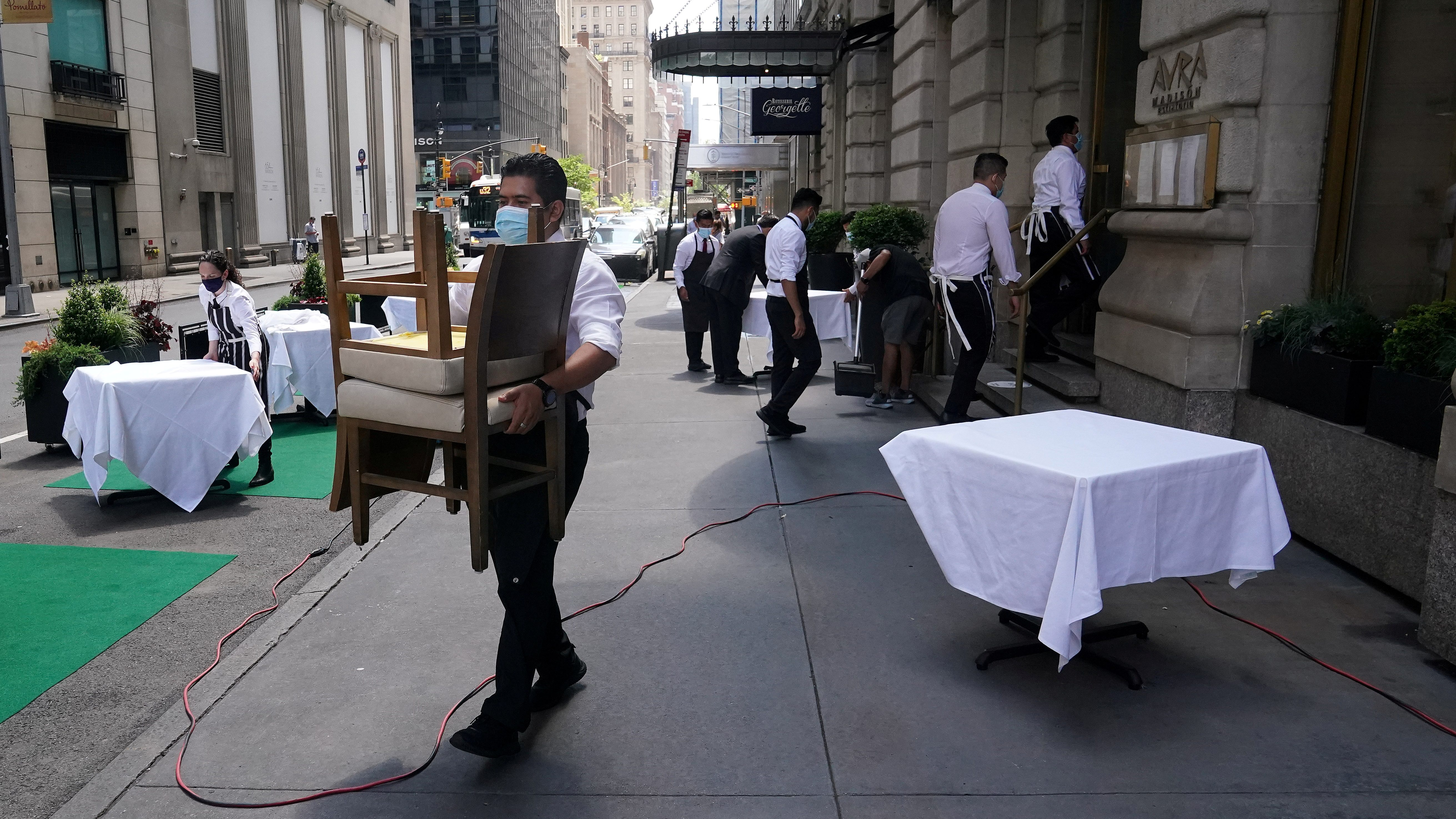 A waiter sets up tables in front of a restaurant in New York City.