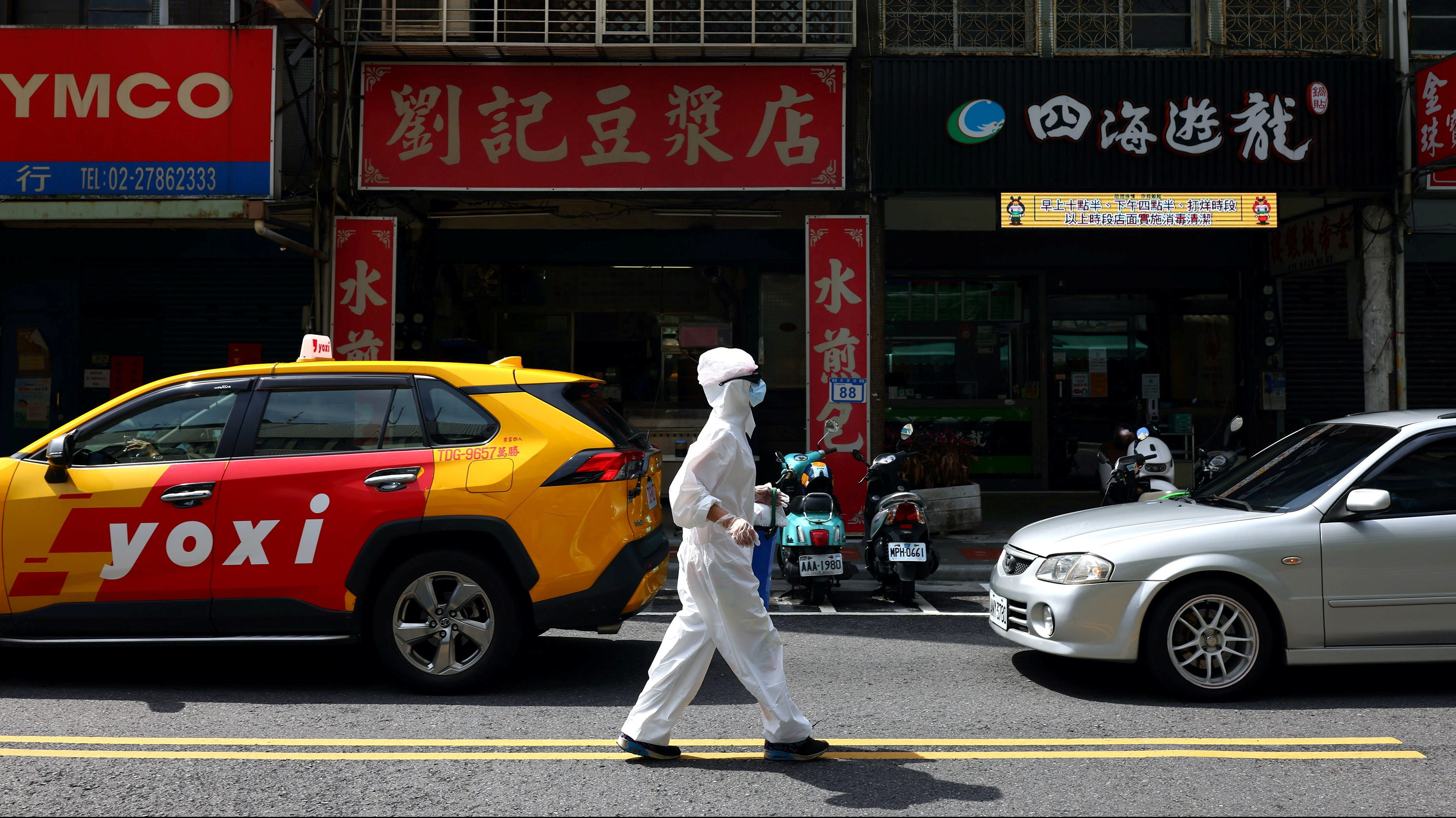 A person dressed in protective suit walks down a street following the recent surge of coronavirus disease (COVID-19) infections in Taipei, Taiwan, June 2, 2021. REUTERS/Ann Wang TPX IMAGES OF THE DAY