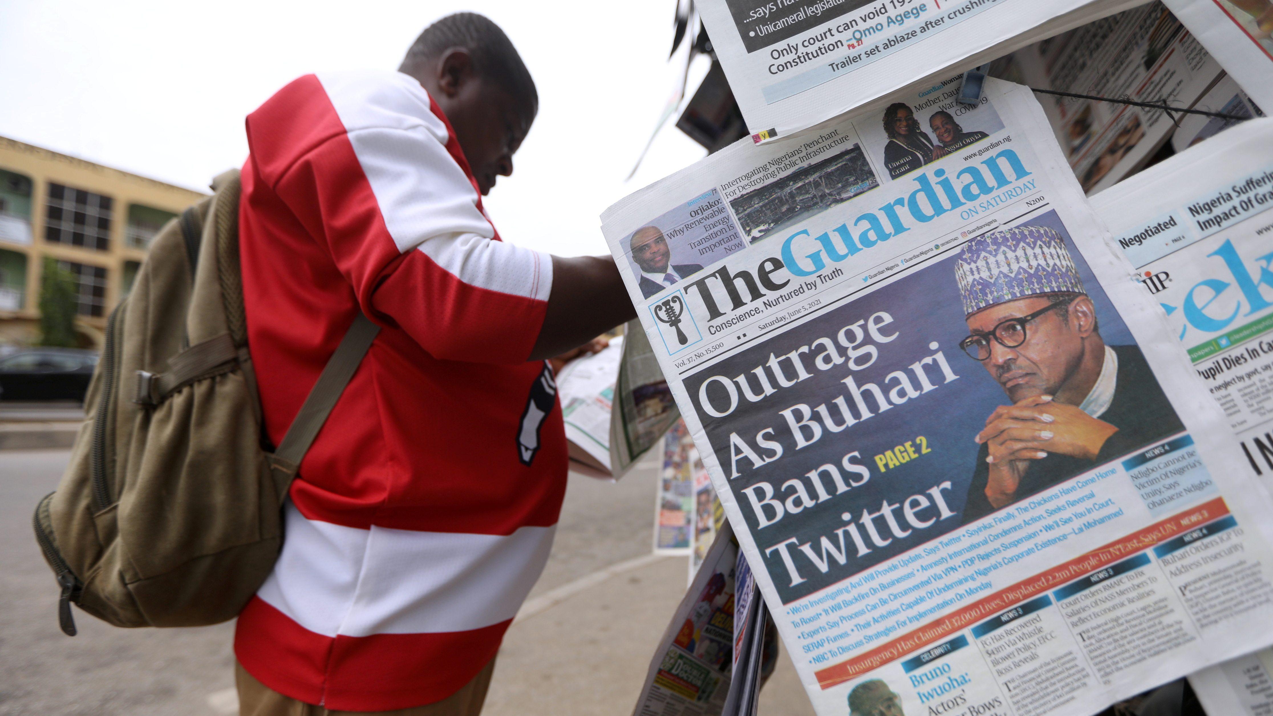 Man reads a newspaper at a newsstand in Abuja