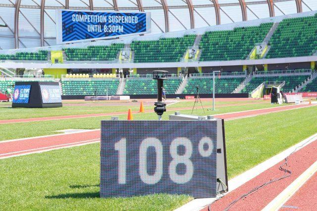 O sinal que mostra uma temperatura de 108 graus está localizado no campo de atletismo abaixo do sinal que diz & quot;