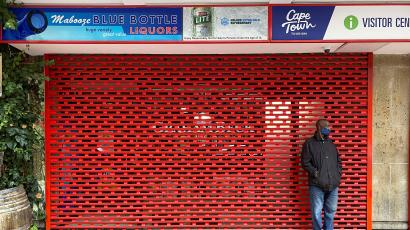 A man stands outside a shuttered liquor store as new coronavirus disease (Covid-19) lockdown restrictions banning the sale of alcohol take effect in Cape Town, South Africa, June 28.