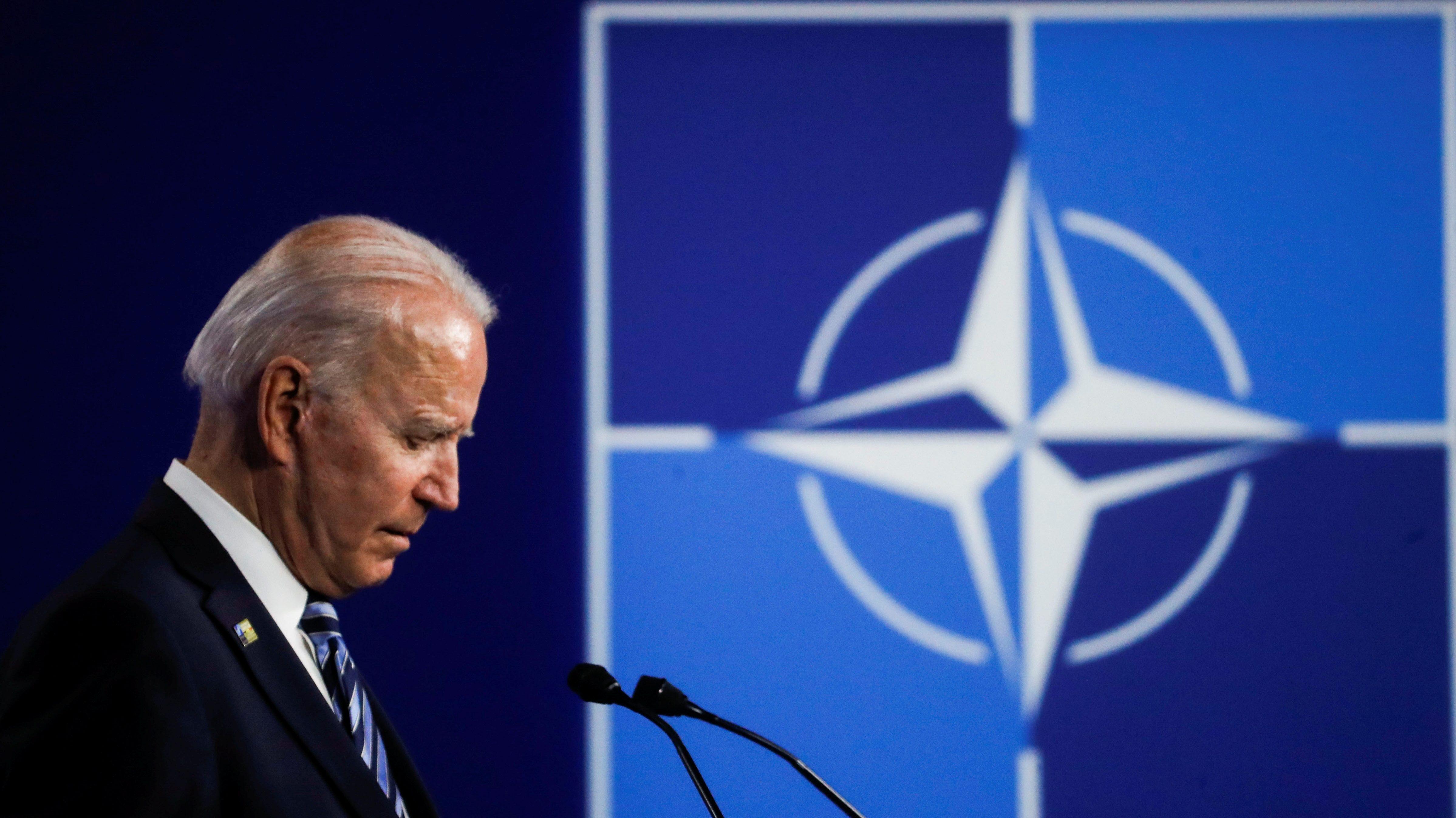 Joe Biden speaks by a NATO sign