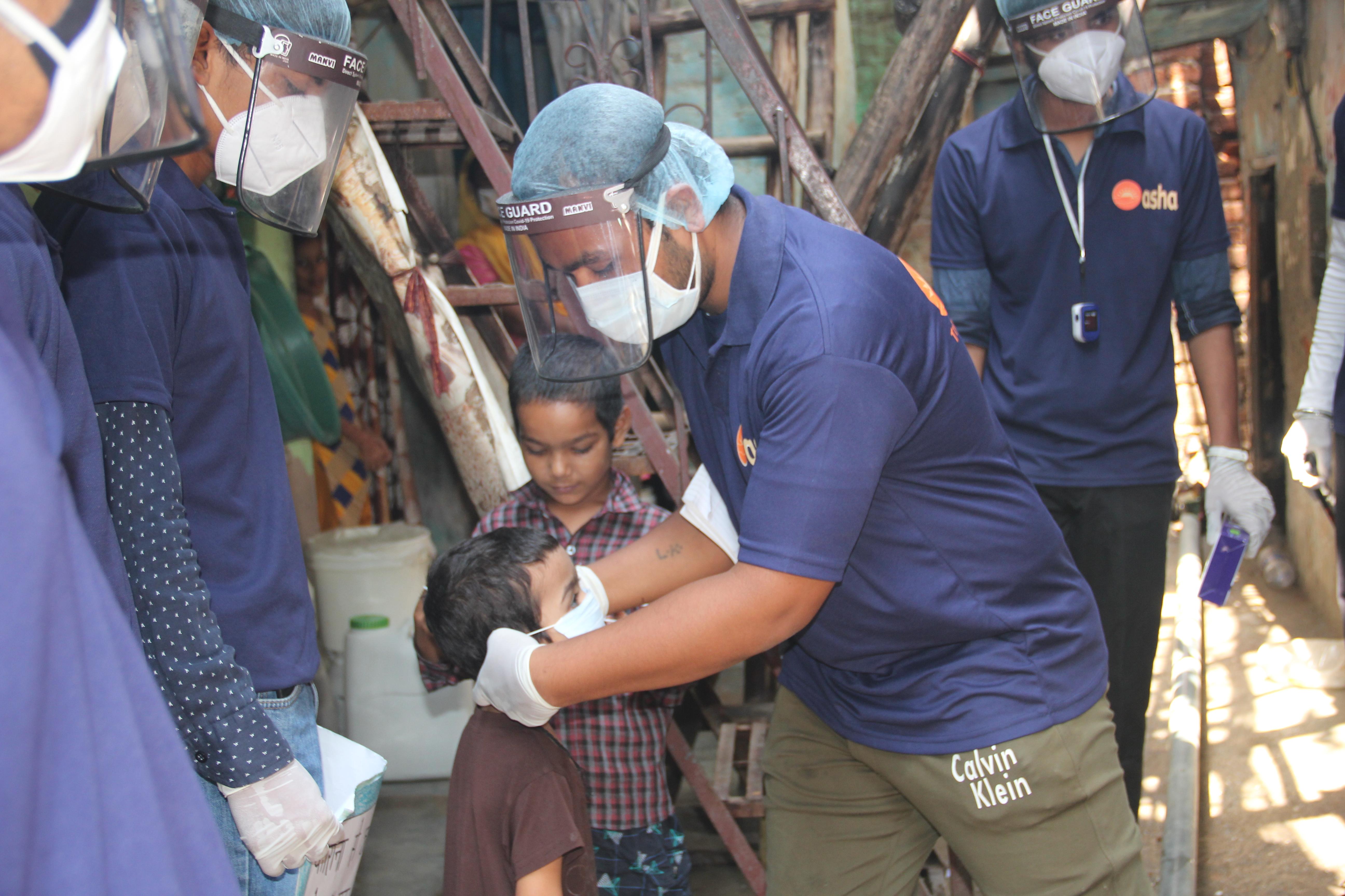Guerreiro Asha coloca uma máscara em um garoto na favela