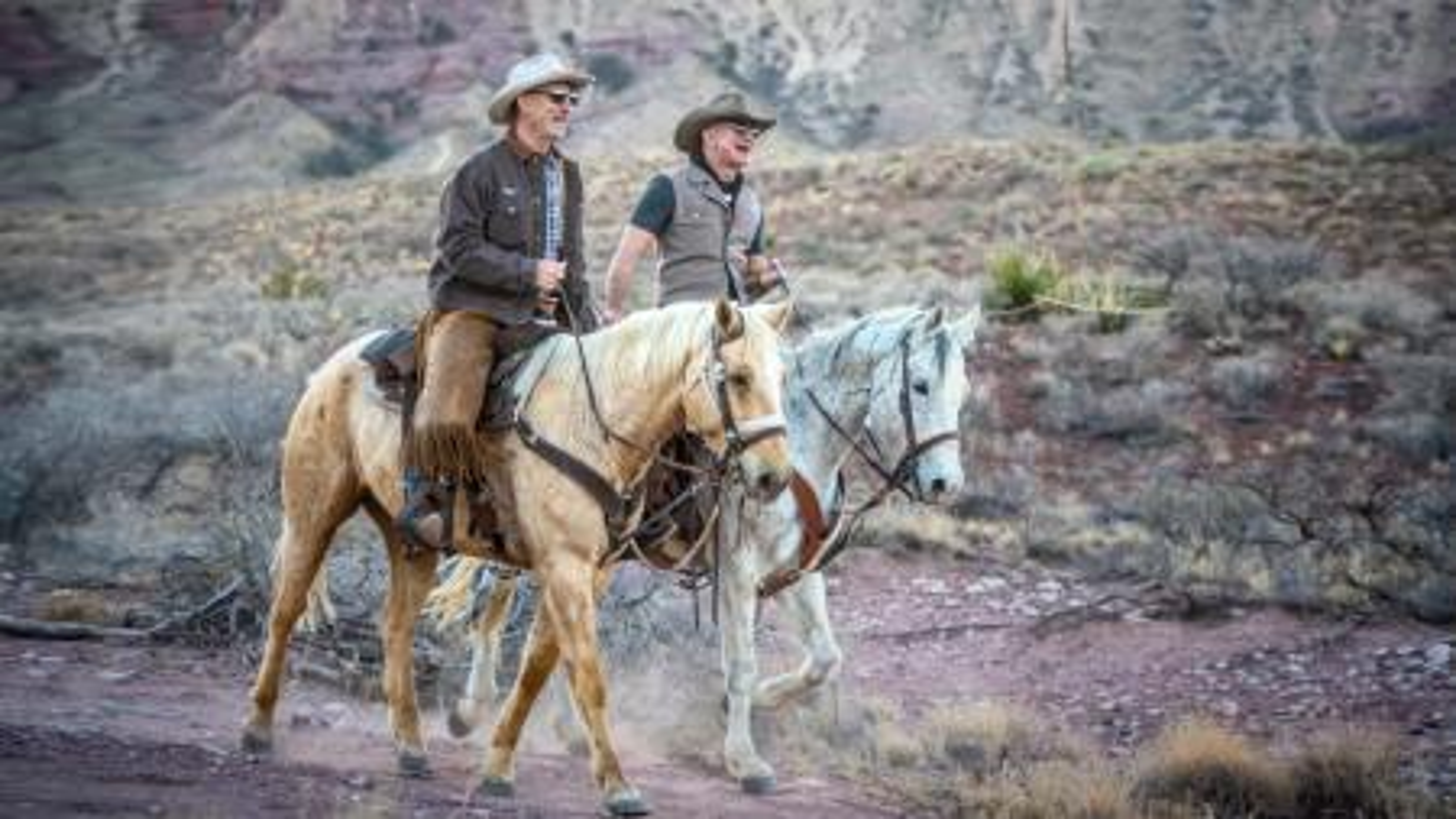 Jeff and Mark Bezos, on horseback.